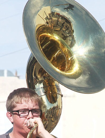 JC AMBERLYN/Miner<BR> The horn offers a reflective view of this Kingman High School student's bandmates Saturday during the Andy Devine Days Parade.