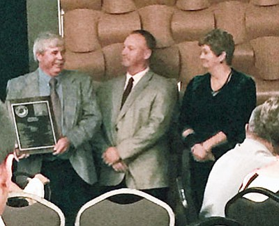 Former Kingman High School athletic director Tim Casson, left, receives his Hall of Fame plaque at the AIAAA annual conference in Prescott last month. (Courtesy)