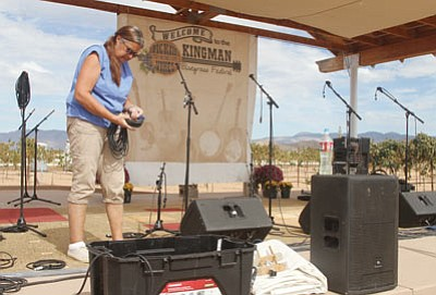 Cate Plante sets up the stage for the festival early Thursday afternoon. (JC AMBERLYN/Miner)