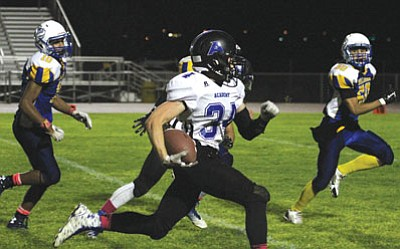 JC AMBERLYN/Miner<BR> Academy's Clayton Holloway escapes the Kingman defense for some of his 209 yards rushing in the Tigers' 49-14 win Friday at KHS. Holloway scored three touchdowns, including an 85-yard interception return.