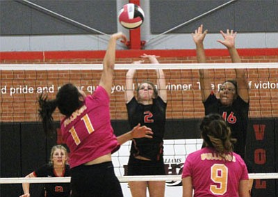 Kingman High's Desirae Gonzalez (11) goes for a kill through the blocks of Lee Williams' Holly McFadyen (2) and Chania Scott (16), as Aurora Camacho (9) and Lee Williams' Sadie Snay (back) prepare to react. Kingman won the five-set thriller 18-25, 18-25, 25-18, 25-20, 15-6. (JC AMBERLYN/Miner)