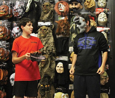 Matt, 14, and Jake Popeil, 18, look through costumes Tuesday at The Spirit Halloween Store in Kingman.