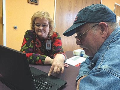 Connie Potter, credit counselor for Kingman Regional Medical Center's patient financial services, helps John Perry sign up for Obamacare during last year's health care enrollment fair at KRMC Professional Medical Building. (HUBBLE RAY SMITH/Miner)