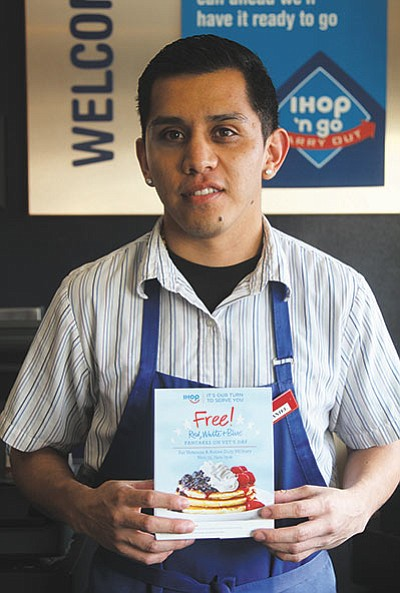 Daniel White holds a sign at IHOP Tuesday showing the restaurant's special for Veterans Day. Several businesses are joining in the effort. (JC AMBERLYN/ Miner)