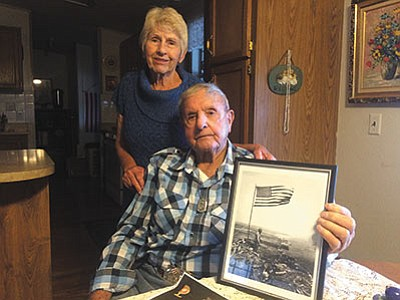 Al Eutsey and his wife, Sandy, with a photo of the first American flag raised over Iwo Jima in  February 1945. (HUBBLE RAY SMITH/Miner)