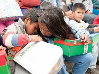 Two children in Ecuador share a peek inside each other's boxes from Operation Christmas Child. (Courtesy)