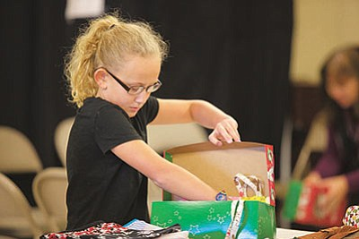 Madison King finds the right gifts to put into her box. (RYAN ABELLA/Miner)