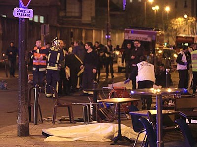 Thibault Camus/The AP<br> Rescue workers and medics work by victims in a Paris restaurant, Friday, Nov. 13. Police officials in France reported a shootout in a Paris restaurant and an explosion in a bar near a Paris stadium. It was unclear if the events were linked.