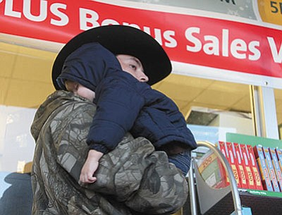 Ray Murphy Jr. holds Dawson Murphy, 3, who seemed plumb tuckered out, as he shops in front of Hastings Entertainment Friday. (JC AMBERLYN/Miner)