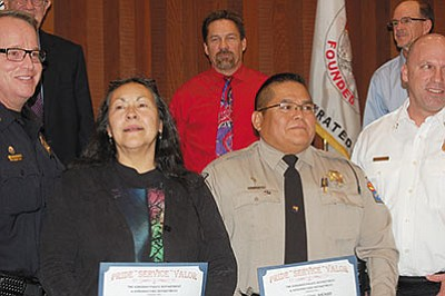 Flanked on the left by Deputy Police Chief Rusty Cooper and Fire Chief Jake Rhoades on the right, Ellen Baca and trooper Leo Becenti Jr. hold their lifesaving awards at Tuesday's City Council meeting in an emotional presentation. (DOUG McMURDO/Miner)