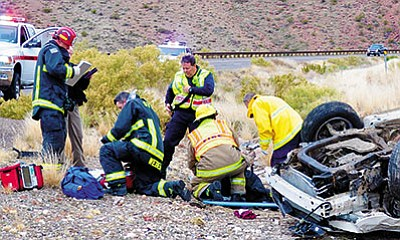 Firefighter-paramedics with the Golden Valley and Bullhead City fire departments treat a teenager who was ejected after she rolled her car on Highway 68 Monday afternoon. (BUTCH MERIWETHER/Courtesy)