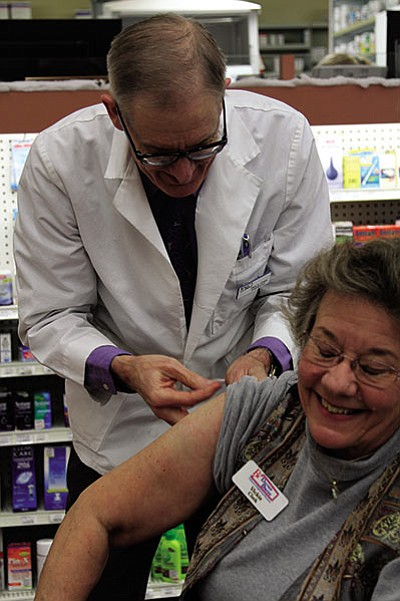 Pharmacist Paul Lewis demonstrates prepping someone for a flu shot at Uptown Drug on Tuesday on Vickie Conway. (JC AMBERLYN/Miner)