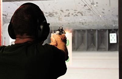 Dale Sills fires a handgun at the Bank Street Guns gun range Tuesday. (JC AMBERLYN/Miner)