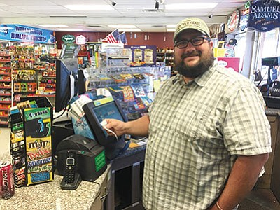 Rhet Pond of Quik Stop on Hualapai Mountain Road sells one of many a Powerball tickets Monday. The gas station has been busy with many people coming in to buy a ticket for the projected $1.4 billion jackpot. (RYAN ABELLA/Miner)