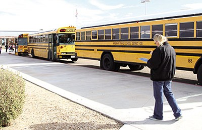 JC AMBERLYN/Miner<BR>Jean Drumal checks a list as teachers lead students to board school buses at Desert Willow Elementary School Thursday afternoon.