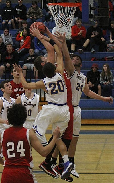 Lee Williams' Chaise Shropshire battles Kingman's Elijah Howery (20) and Anthony Pinto (24) for a rebound during Lee Williams' win over the Bulldogs Tuesday at KHS, 41-27. (JC AMBERLYN/Miner)