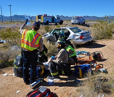 BUTCH MERIWETHER/Courtesy<BR> Golden Valley Fire District Firefighters attend to a severely injured female driver who was involved in a two-vehicle accident that occurred at 11:15 a.m. today at the intersection of Milky Way Road and Highway 68.