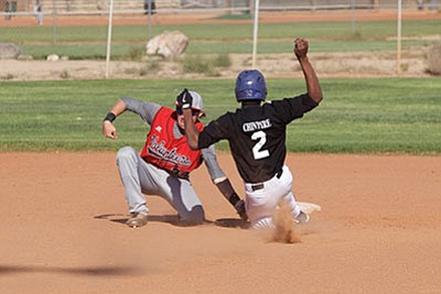 Kingman Academy's Jeffry Chinyere slides into the waiting tag of Lee Williams' shortstop Paul Giglio during last year's April 8 game at Southside Park. Both players are back for the 2016 season. (File photo)