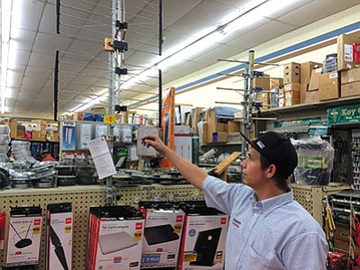 "HUBBLE RAY SMITH/Miner<BR> Elvin Gumfory, sales clerk in the electronics department at True Value Hardware in Kingman, shows some of the more expensive outdoor antennas that can pick up 27 over-the-air channels. Antenna prices range from $10 for indoor ""rabbit ears"" to more than $100 for some of the higher quality outdoor antennas."