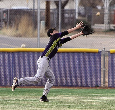 Kingman's Luke Ness chases down a flyball during Thursday's game against Chinle in the KHS Baseball Invitational Tournament.
