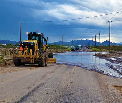 BUTCH MERIWETHER/For the Miner<BR> Mohave County Public Works prepares to take care of flooding on South Estrella Road in Golden Valley after a recent storm.
