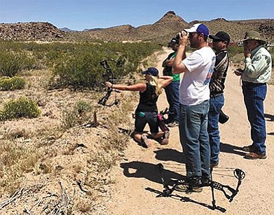 "This group of archers watches as a fellow archer takes aim during the ""smoker round"" at a recent archery shoot at the Mohave Sportsman Club's 7 Mile Hill Range. (Courtesy)"