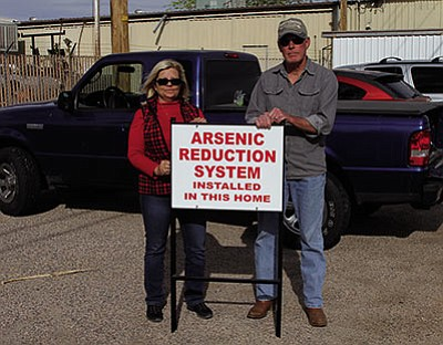 Dawn and Jerry Hill stand with a sign they had made in Kingman, notifying neighbors about steps they took to remove the arsenic from their water. (JC AMBERLYN/Miner)