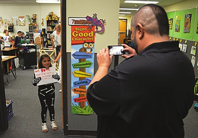 AARON RICCA/Miner<br> Gabriel Sanchez snaps a photograph of his daughter, Hualapai Elementary 2nd-grader Layla Sanchez before the Vocabulary Parade Friday.