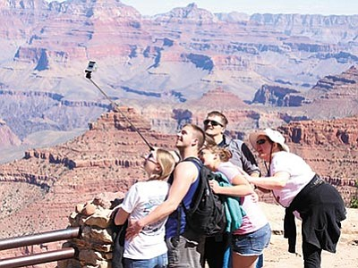 Tourists pose for a selfie in Grand Canyon National Park, which set an attendance record last year with more than 5.5 million visitors. (SOPHIA KUNTHARA/Cronkite News)