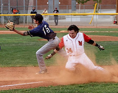 Lee Williams' Paul Giglio slides safely into third base with a triple past Kingman High third baseman Luke Ness in the fourth inning of the Volunteers' 8-1 win over the Bulldogs Thursday at LWHS.