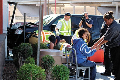 Firefighters and paramedics tend to one of two men who were injured at McDonald's Wednesday after a woman accidentally drove into the restaurant's entrance. To the right, a restaurant manager comforts the driver, a 69-year-old Indiana resident. (DOUG McMURDO/Miner)