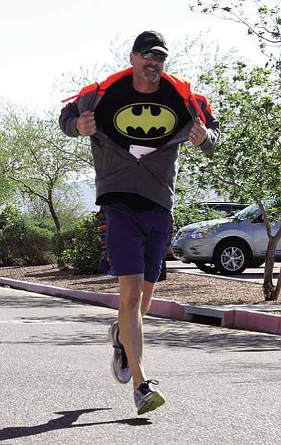 JC AMBERLYN/Miner<BR> Mike Kebble flashes a Batman logo during the Superhero 5K Run/Walk and Kids Dash in 2016. He was at the race with his wife Kristin and wanted to send thanks to a girl they met named Sunflower who helped inspire his wife to finish the race.
