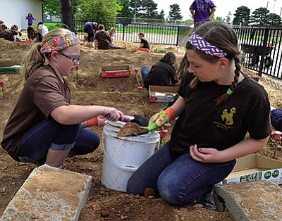 "Abby Zoll (left) and Sawyer Preston (right) shovel dirt back into a pit after uncovering previously buried ""artifacts."" (AARON RICCA/Miner)"