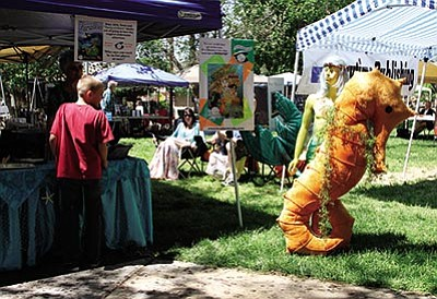 Larry Hayes Jr., 10, looks at a merman character at book author Melany Holton's booth Saturday at Metcalfe Park. (JC AMBERLYN/Miner)