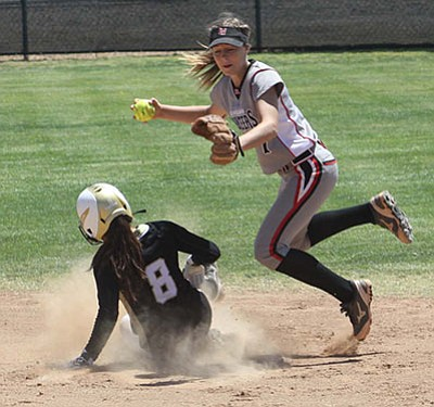 Jasmine Murguia of Douglas slides into second base in an effort to break up the double play throw from Tori Lorgan of Lee Williams in the fourth inning of the first round of the D-III state playoffs in Douglas Saturday. Douglas won the game 15-0. (BRUCE WHETTEN/Douglas Dispatch)