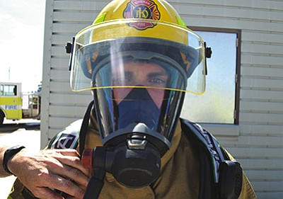 Firefighter/trainee Alex Gabler has the seal of his facemask checked shortly after a timed drill.  (AARON RICCA/Miner)