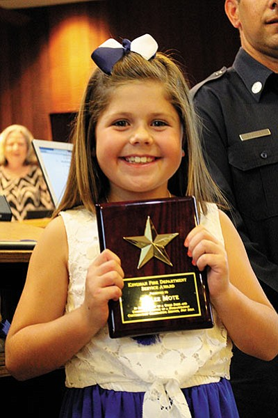 Taylee Mote, 8, is all smiles as she holds the Kingman Fire Department Service Award she received at Tuesday's City Council meeting. Mote ran a stunningly successful one-day lemonade stand on March 5 that raised more than $550 for the family of Natalie Willard, a toddler stricken with cancer. (DOUG McMURDO/Miner)