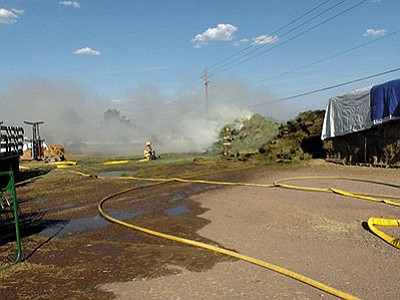 A Kingman firefighter puts water on burning hay Saturday afternoon at Stockton Hill Hay and Feed. Investigators said the fire was suspicious in nature. (Courtesy)