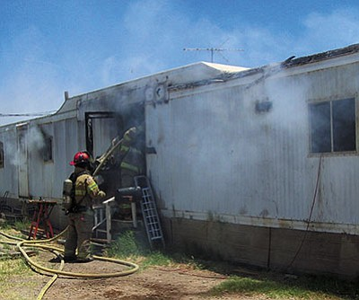 A firefighter with the Northern Arizona Consolidated Fire District puts water on a house fire Sunday. (Courtesy)