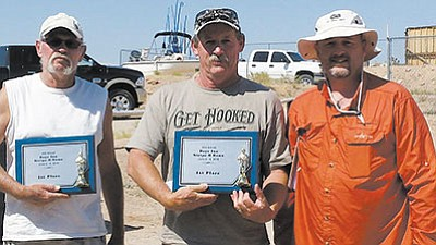 Charlie Suttles, left, and Mike Van Zandt, middle, captured the Stripe-R-Rama tournament with more than 40 striped bass weighing in at over 91 pounds. Tournament director Johnnie Hoeft presents their trophies. (DON MARTIN/For the Miner)