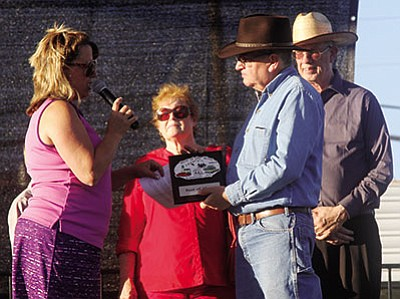 "Dora Manley presents Jim Hinckley with a plaque naming him ""King of the Mother Road 2015"" as City Councilwoman Carole Young and Mayor Richard Anderson watch last September. Hinckley is going to Germany to sell Route 66 and Kingman. (JC AMBERLYN/Miner)"