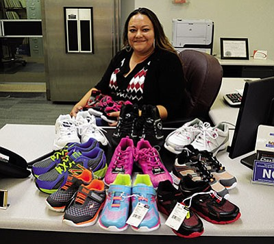 Mohave Community Federal Credit Union employee and 'Kicks for Kids Shoe Drive' organizer Ramona Baptista shows off some of the shoes she's received since June 1. AARON RICCA/Miner