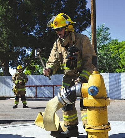 Reporter Aaron Ricca attaches a large diameter hose for water supply from hydrant to truck to attack line hose. (MAC NELSON/KFD)