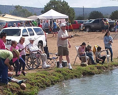 Roy Dunton, seated, and Scott Dunton (with fishing rod) were out and testing the waters at the Fishing For Smiles event. The Dunton family has donated the use of their pond for four years, and have pledged to allow the event organizers use it as long as necessary. (DON MARTIN/For the Miner)