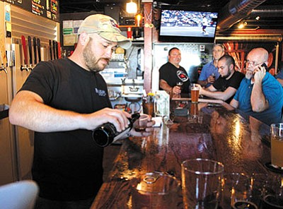 Black Bridge Brewery's Tim Schritter pours a sample of his latest beer Thursday in downtown Kingman. (ALAN CHOATE/Miner)