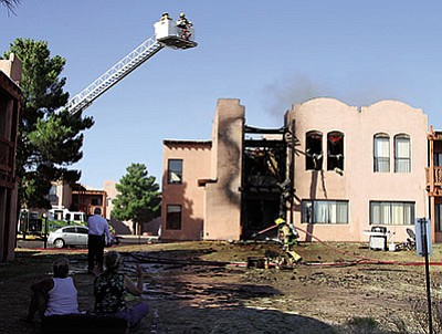 Flames are visible through a window at Thursday's fire at Copper Ridge Apartments. (JC AMBERLYN/Miner)