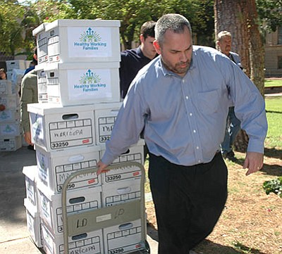 State Elections Director Eric Spencer hauls boxes of petitions submitted Thursday. (HOWARD FISCHER/Capitol Media Services)