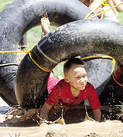 Oscar Smith splashes through a tire obstacle during last year's Mighty Mud Mania at Firefighters Park. The event returns on Thursday. (JC AMBERLYN/Miner)