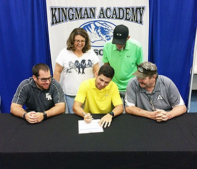 Tristen Pits, in yellow, signs his letter of intent with Texas Wesleyan University last Sunday as Kingman Academy High School athletic director Michael Perrine (sitting left), parents Leigh and Levi Pitts (standing), and KAHS football coach Dan Stroup enjoy the moment with him. (SHAWN BYRNE/Miner)
