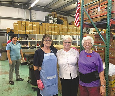 Volunteer Faye Masters (from left), Executive Director Catherine Walker and Jeri Stoll pause in front of the food bank's inventory. The food bank desperately needs more volunteers. To become a volunteer, visit the Kingman Food Bank at 2930 E. Butler Ave. and fill out an application. (CODY DAVIS/Miner)